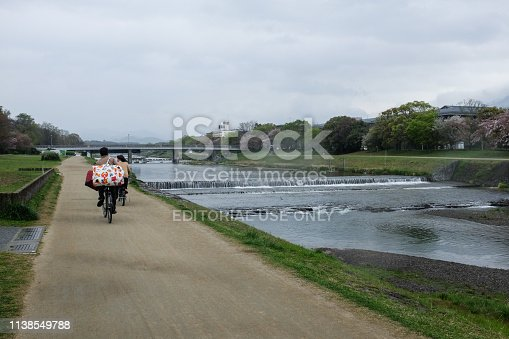 969439086 istock photo Cyclists carry baggages and travel on the road along the Kamogawa River on a rainy day in Kyoto. 1138549788