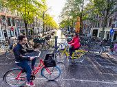 Amsterdam, Netherlands - 23 September 2019: Bicycle riders are passing a canal bridge in Amsterdam's old Jordaan quarter (Egelantiersgracht)