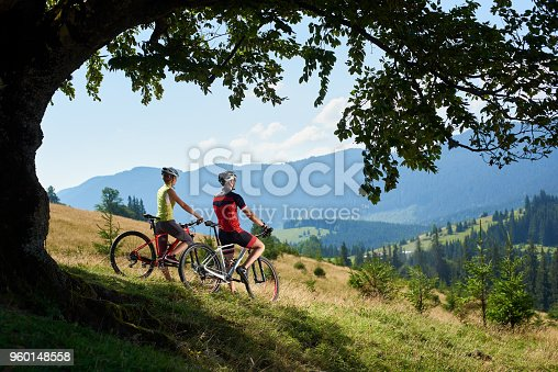 istock Cyclists, man and woman in helmets and full equipment, standing with bikes on grassy hill 960148558