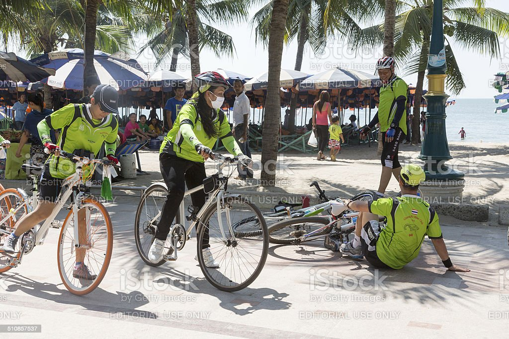 Cyclists on the beach in Bang Saen, Thailand, one overturned. stock photo