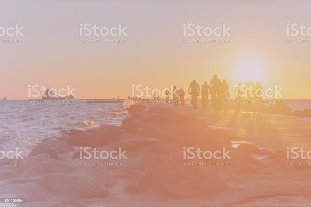 Cyclists on the pier in the sea at sunset royalty-free stock photo