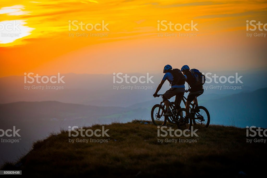 Cyclists on the Top of Mountain at Sunset stock photo