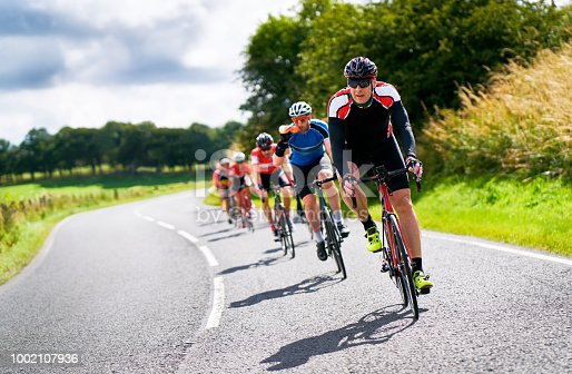 Cyclists racing on country roads on a sunny day in the UK.Cyclists racing on country roads on a sunny day in the UK.