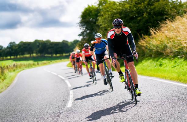 ciclisti che corrono su strade di campagna. - ciclismo foto e immagini stock