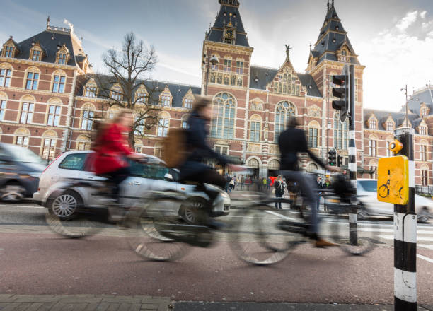 Cyclists ride in Amsterdam street in front of the Rijksmuseum stock photo