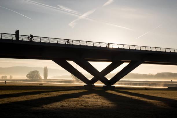 radfahrer fahren morgens im nebel und sonnenaufgang über eine brücke - radwege deutschland stock-fotos und bilder