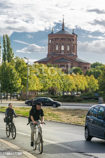 BERLIN, GERMANY - July 28, 2018: Cyclists riding at the quiet streets in front of the Protestant Saint Thomas Church, at Kreuzberg, Mariannenpl, which was once the largest church in Berlin.
