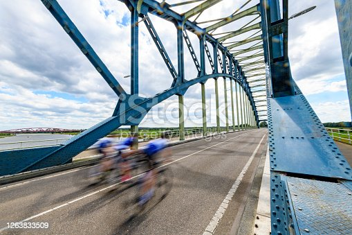 Cyclists riding over the Old IJsselbrug over the river IJssel between Zwolle and Hattem. View from the middle of the road on the old steel arch bridge.