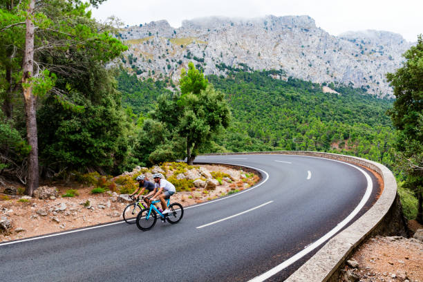 cyclists riding up the puig major peak in majorca - mallorca stock photos and pictures