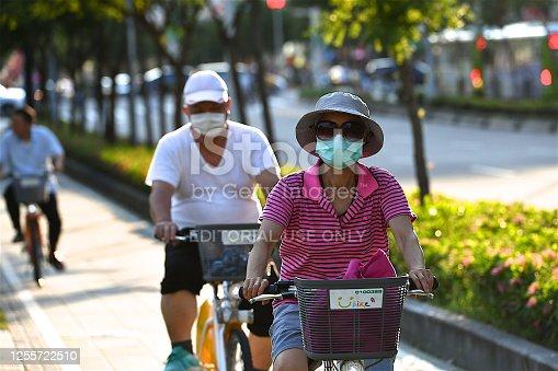 Taipei, Taiwan-07 12 2020:Cyclists wearing protective face masks on a street in Taipei city, Taiwan, during the global coronavirus epidemic.