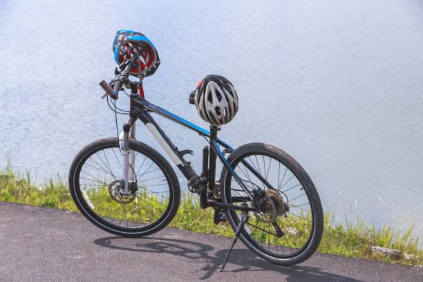 cyclo cross fahrrad mit helm, stehen an der straße in der nähe von reservoir - cyclocross stock-fotos und bilder