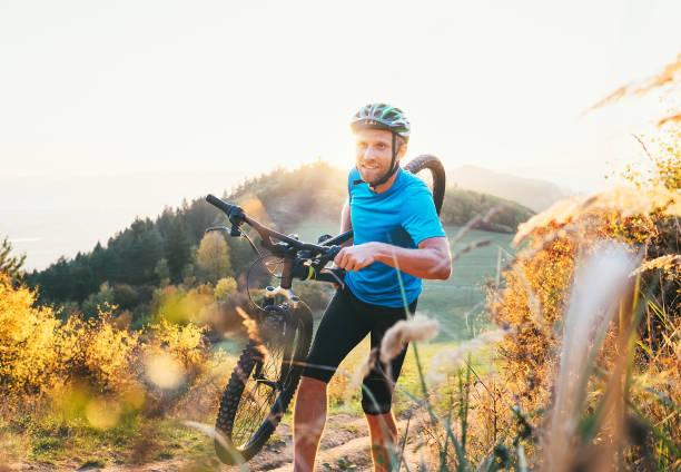querfeldein-wettbewerb mitglied mann mountainbiker mit seinem motorrad bis auf hügel - cyclocross stock-fotos und bilder