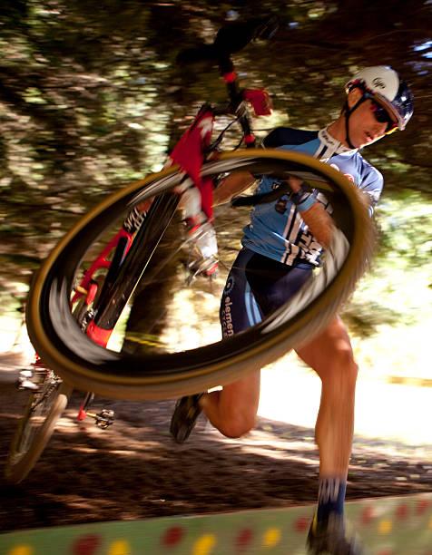 cyclone hudhud racer tragen sein bike über hindernisse - cyclocross stock-fotos und bilder