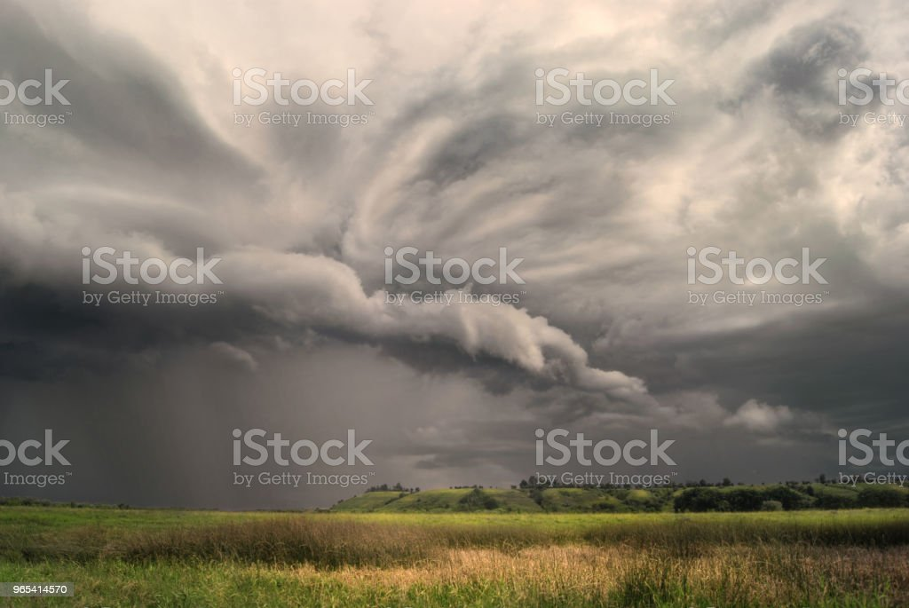 Cyclone storm over fields and meadows approaches the hilly valley. Rainy cloudy day zbiór zdjęć royalty-free