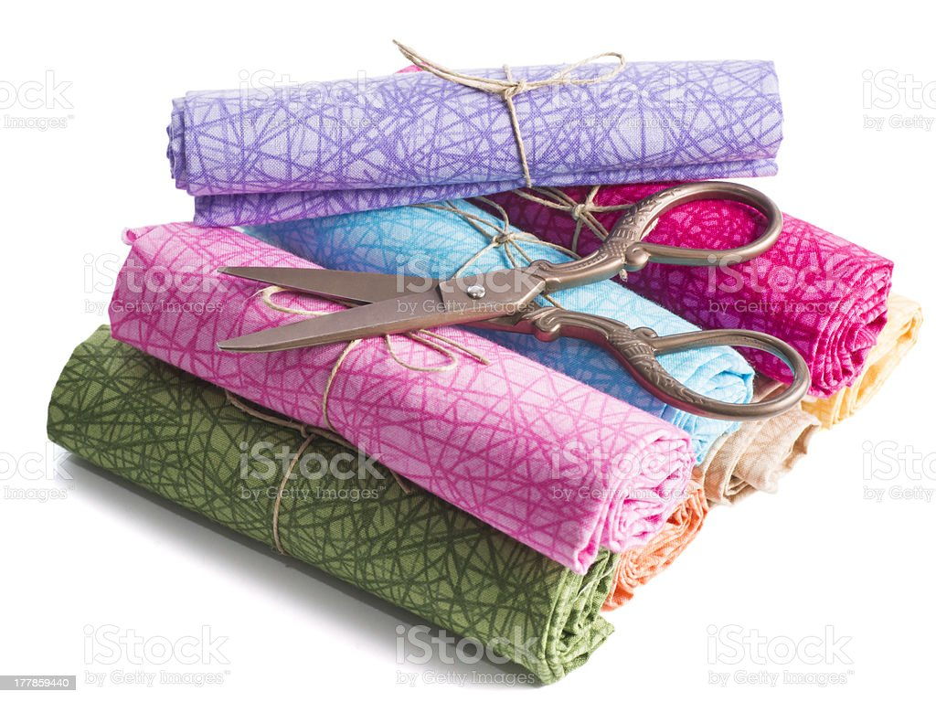 Cylinders of Colorful Fabric and Metal Scissors royalty-free stock photo