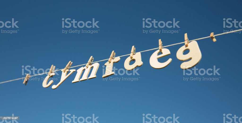 Cymraeg spelt out on a clothesline with pegs holding letters stock photo