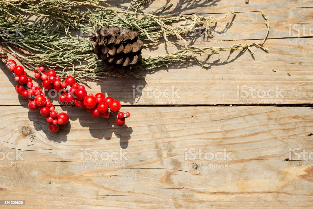 cypress branch, fir-cone and red berries on old wooden table. New year concept stock photo