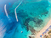 Cyprus beautiful coastline, Mediterranean sea of turquoise color. top view, aerial view. water bikes ride on crystal clear water near the beach with umbrellas and sun loungers.
