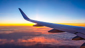 A colorful sunrise seen from the plane window. Sun is raising from the clouds, painting them pink and orange. Horizon line turns yellow with the sunbeams. Plane wing covering the sun. Romantic view