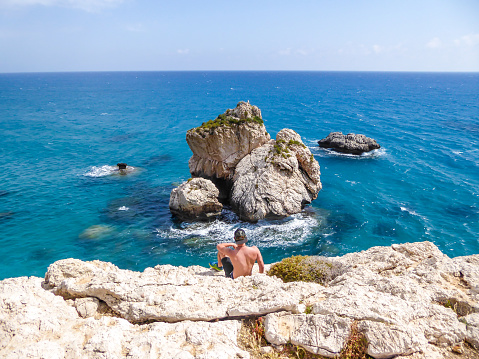 istock Cyprus - Young man sitting at a steep cliff with a sea view 1155949788