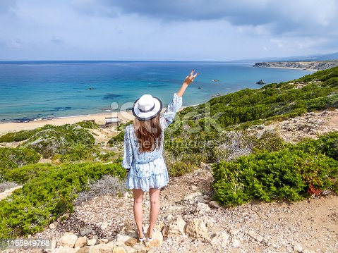 Woman wearing a hat enjoying the view on Lara Beach, Cyprus from above. Hidden gem, not spoiled by tourists. Solitude, calm feelings, waves gently spreading on the beach. turquoise color of the water