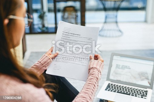 Shot of a woman reading a letter of unemployment