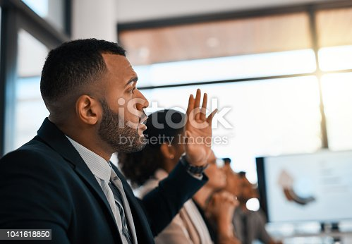 Shot of a young businessman raising his hand during a meeting in an office