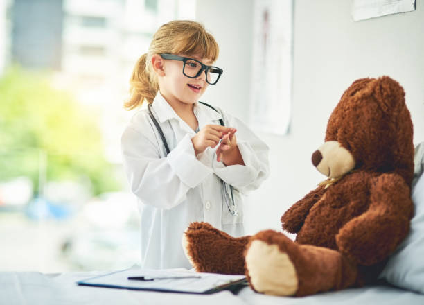 I'd like to see you for a follow up, Teddy Shot of an adorable little girl dressed up as a doctor and examining a teddy bear dressing up stock pictures, royalty-free photos & images