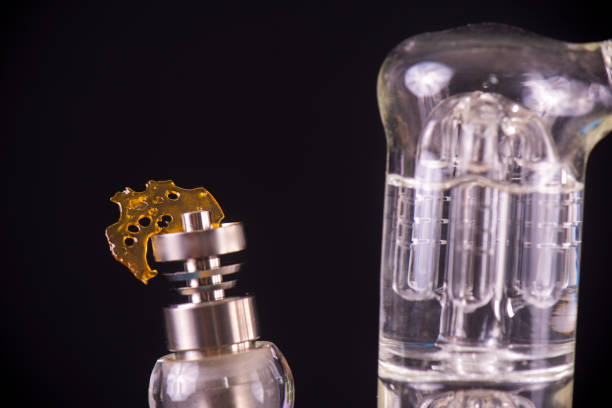 Dabbing tool with small piece of cannabis oil aka shatter - medical marijuana concentrates concept stock photo