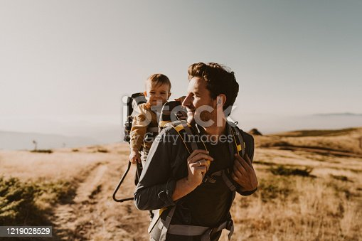 Photo of young father spending time with his son by taking him on a hike while he is in a baby carrier backpack