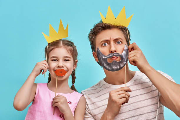 dad and child are holding paper crown - papa humor stock-fotos und bilder