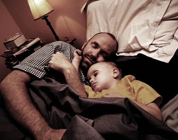 vater und kind schnell asleep - nachttischleuchte touch stock-fotos und bilder