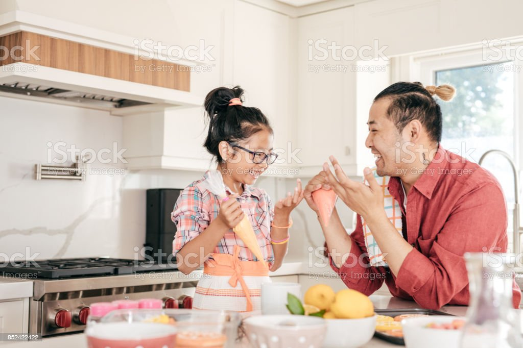 Dad and daughter baking cookies together stock photo