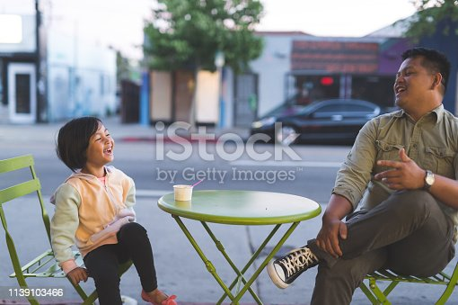 A Filipino dad and his young daughter sit at an outdoors table at an ice cream shop in the city. She is eating a bowl of ice cream and looking across the table at him while they laugh uproariously together about something funny.