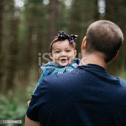 Father's Day portraits of a loving father and daughter. The baby girl is half hispanic/latino and half Caucasian. Father is wearing a casual navy blue shirt and has glasses and tattoos on his arms. They are in a tree covered forested area outdoors.