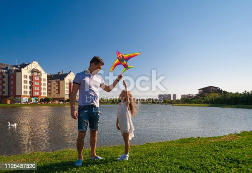 665586146istockphoto Dad and daughter, kite, landscape city 1125437320