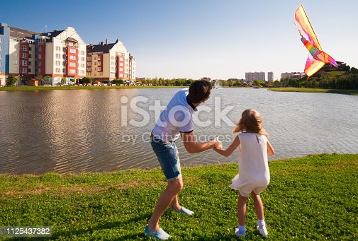 665586146istockphoto Dad and daughter, kite, landscape city 1125437382