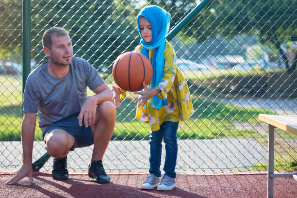 Dad and daughter on a basketball court stock photo