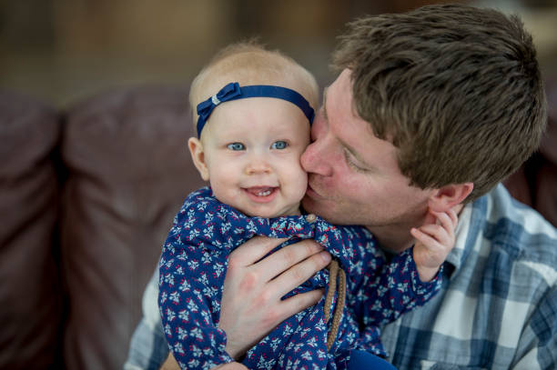 Dad And Daughter A Caucasian father and baby girl are indoors in their living room. The father is holding his daughter and kissing her on the cheek. little girl kissing dad on cheek stock pictures, royalty-free photos & images
