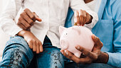 istock Dad and daughter saving money to piggy bank 1135972976
