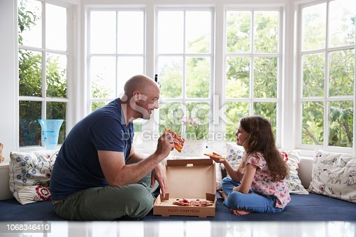Dad and daughter sit on window seat at home sharing a pizza