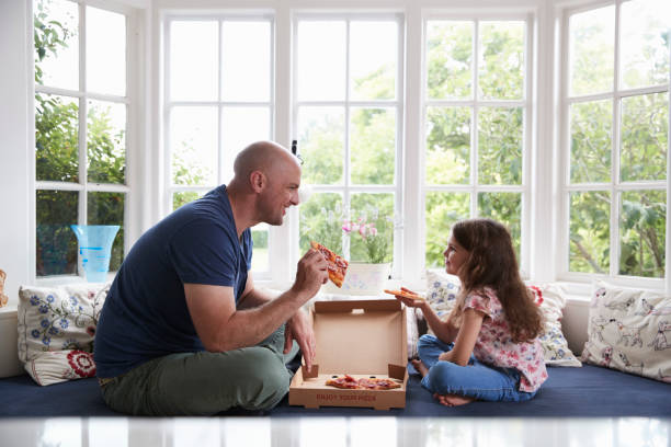 Dad and daughter sit on window seat at home sharing a pizza Dad and daughter sit on window seat at home sharing a pizza shaved head stock pictures, royalty-free photos & images