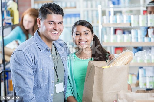 istock Dad and daughter volunteer in local food bank 827810166