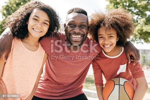 1082195070 istock photo Dad and daughters  posing with basketball ball 811679902