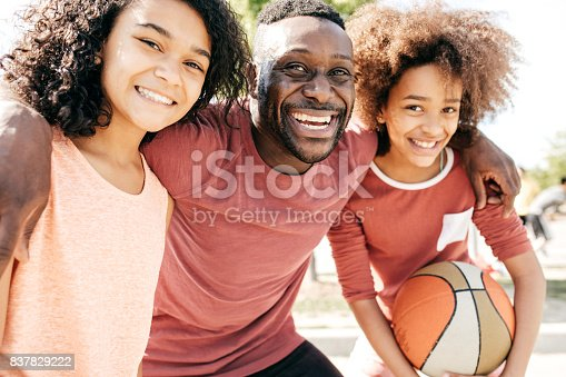 1082195070 istock photo Dad and daughters  posing with basketball ball 837829222