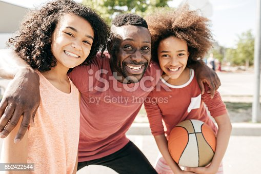 1082195070 istock photo Dad and daughters  posing with basketball ball 852422544