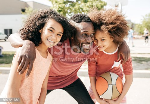 1082195070 istock photo Dad and daughters  posing with basketball ball 860721382