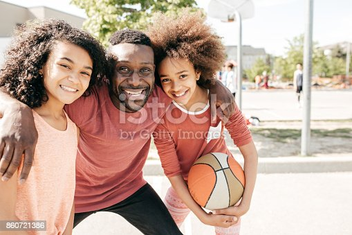 1082195070 istock photo Dad and daughters  posing with basketball ball 860721386