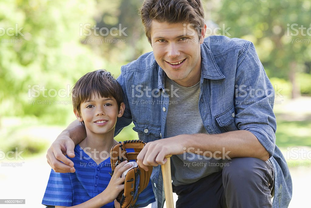 Dad and his boy holding baseball equipment stock photo