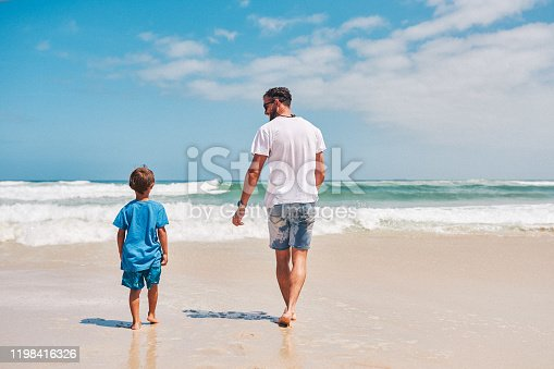 Shot of an adorable little boy having fun with his father at the beach